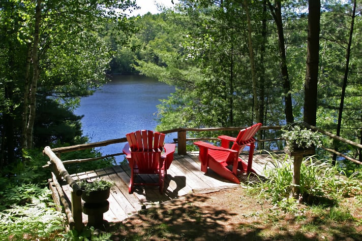 Muskoka chairs on deck overlooking water